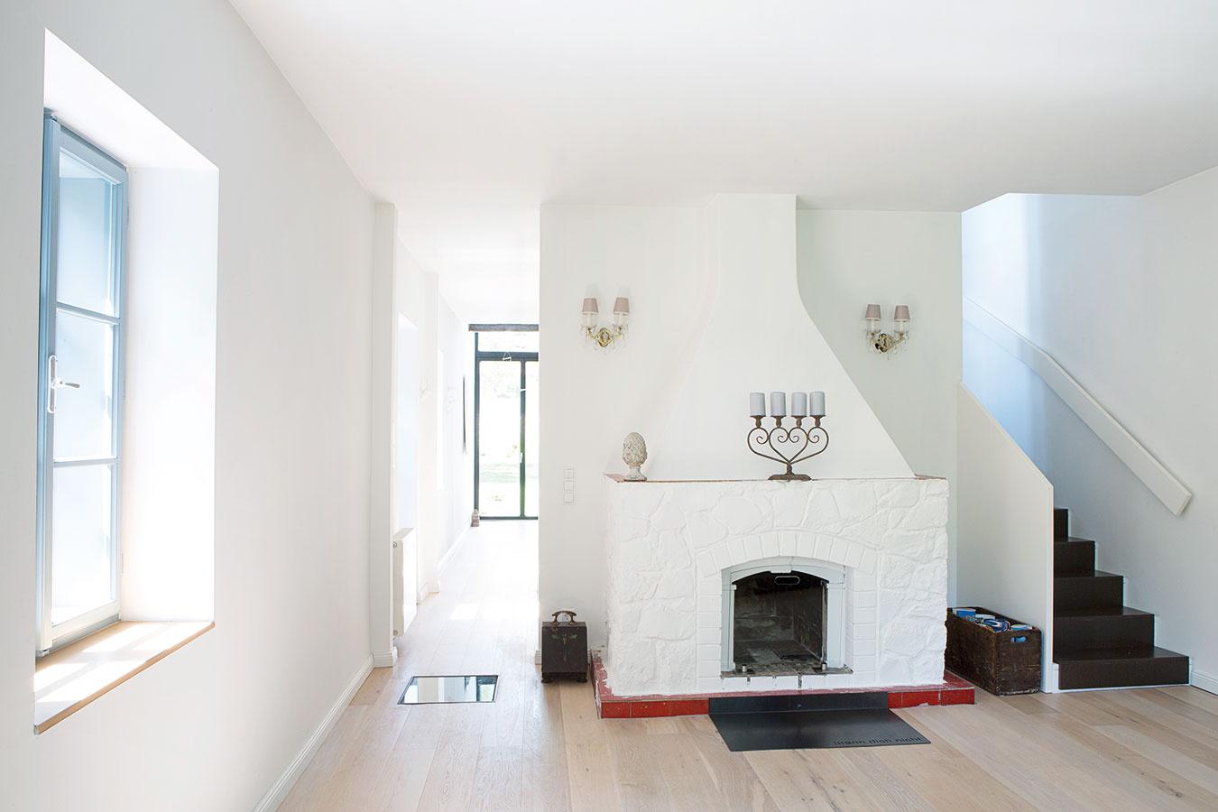 Dominantou obývačky je veľký murovaný kozub, ktorý je tradičným aprirodzeným centrom domácnosti. Okolo neho sa zjednej strany prechádza do kuchyne sjedálňou, zdruhej sa po drevenom schodisku vychádza do podkrovia – aj vďaka riešeniu sminimom dverí vyzerá prízemie otvorene acelistvo.