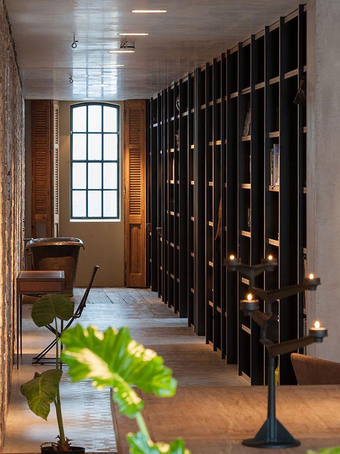 Skutočne netradične – priamo na chodbe – sa nachádza minimalistická kúpeľňa, ktorá je prostredníctvom knižničných políc prepojená so spálňou.