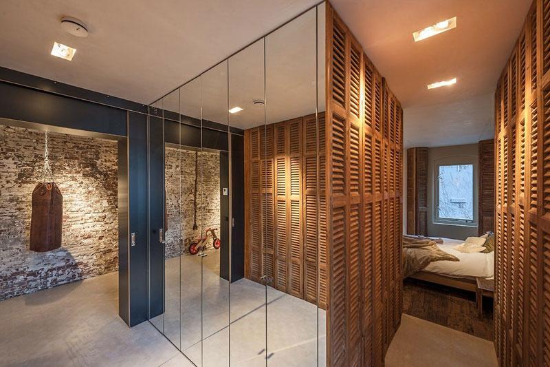Stena pokrytá zrkadlami poblíž spálne ukrýva úložný priestor.