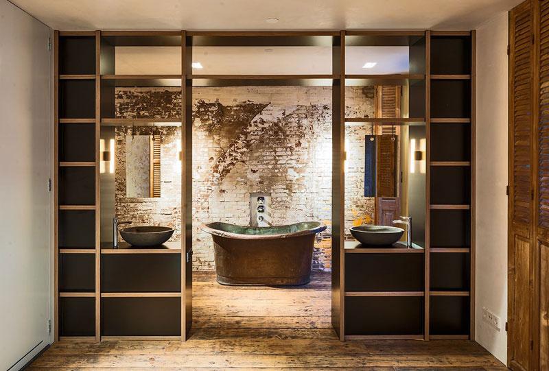 Pri pohľade zo spálne vyzerá kúpeľňa veľmi symetricky a skutočne industriálne. Je tomu tak vďaka surovej stene, ktorá je ponechaná za veľkou kovovou vaňou.