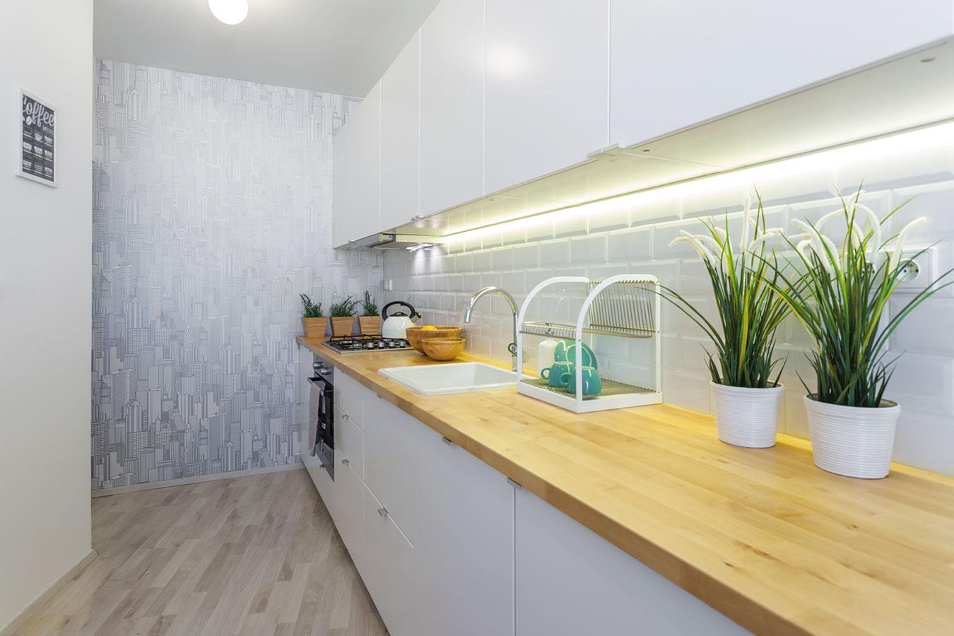 Tapeta decentne oživila jednoducho zariadenú kuchyňu. Na mieste niekdajších dverí vzniklo miesto na chladničku skrytú za rohom.