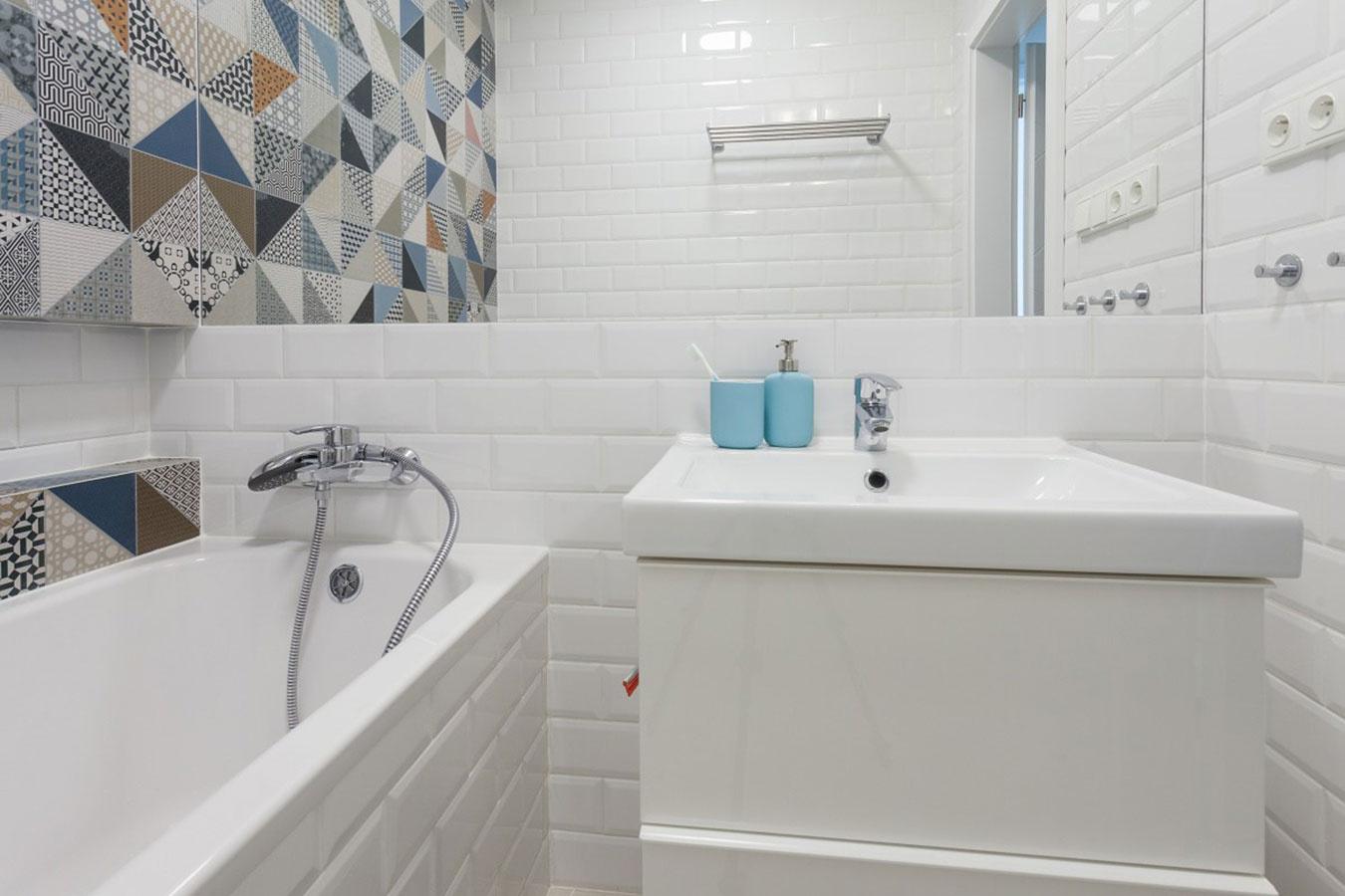 Silný efekt. Aby pomerne malú kúpeľňu opticky zväčšili, použili na jednej stene veľkú tabuľu zrkadla, ktorá siaha od kúta po kút. Na oživenie jednoduchého, cenovo dostupného bieleho obkladu stačí jedna pestrá stena.