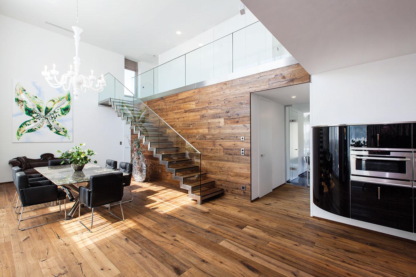 Veľkolepý priestor jedálne vcentre dispozície je vysoký cez dve podlažia – dojem zneho podčiarkuje drevo, ktoré zpodlahy plynulo prechádza až na stenu so schodiskom. Vtomto mieste je prepojené hlavné obytné podlažie sposchodím.