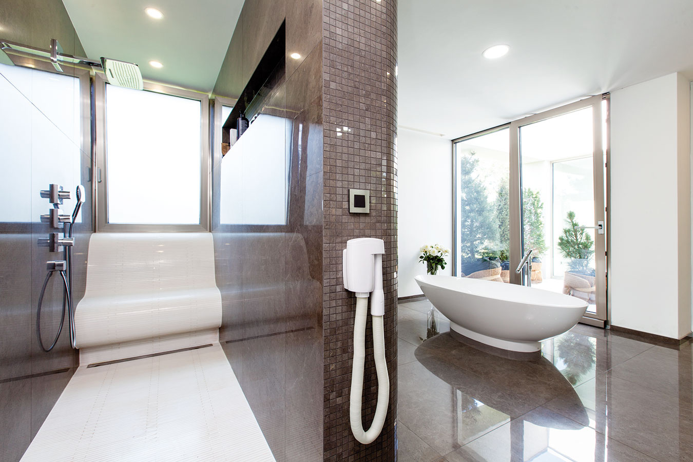 Kúpeľňa en suite sveľkorysými rozmermi, pohodlným sprchovacím kútom aj výhľadom do chráneného bočného patia je súčasťou spálňovej zóny na prízemí.
