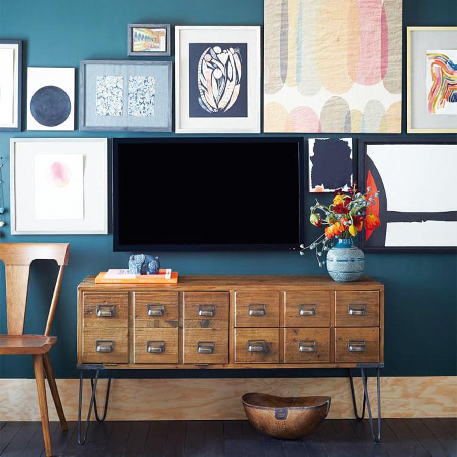 Nechať TV splynúť skompozíciou obrazov je efektný, pomerne často využívaný trik. Čo jej pomôže ešte viac, je tmavé pozadie, na ktorom viac vyniknú svetlé plochy. Vtakom prípade oto viac zažiari kartotečná skrinka.