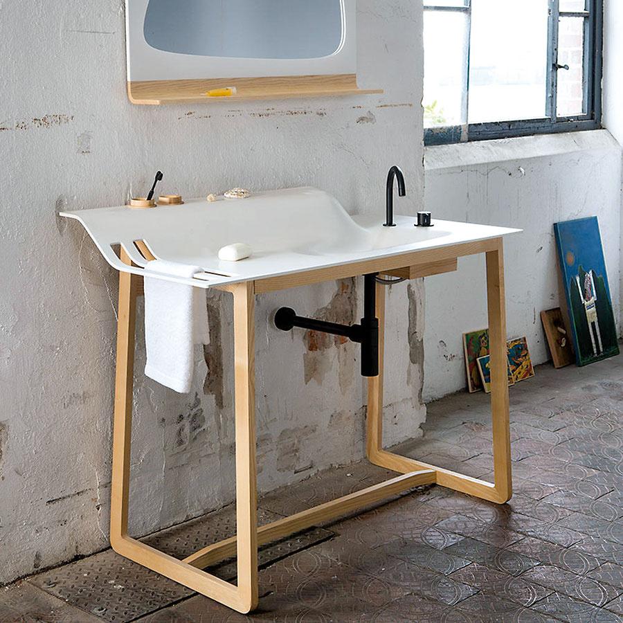 Moderný praktik. Prítomnosť menšieho umývadla alebo krčaha svodou bola vminulosti nevyhnutnou súčasťou každej spálne. Práve týmto prvkom sa inšpirovalo štúdio Ellenbergerdesign, ktoré vytvorilo špeciálny umývací stôl. Konštrukciu zmasívneho dreva dopĺňa umývadlo zumelého kameňa HI-MACS®. Súčasťou stola sú priestory na odloženie uterákov či zubných kefiek.