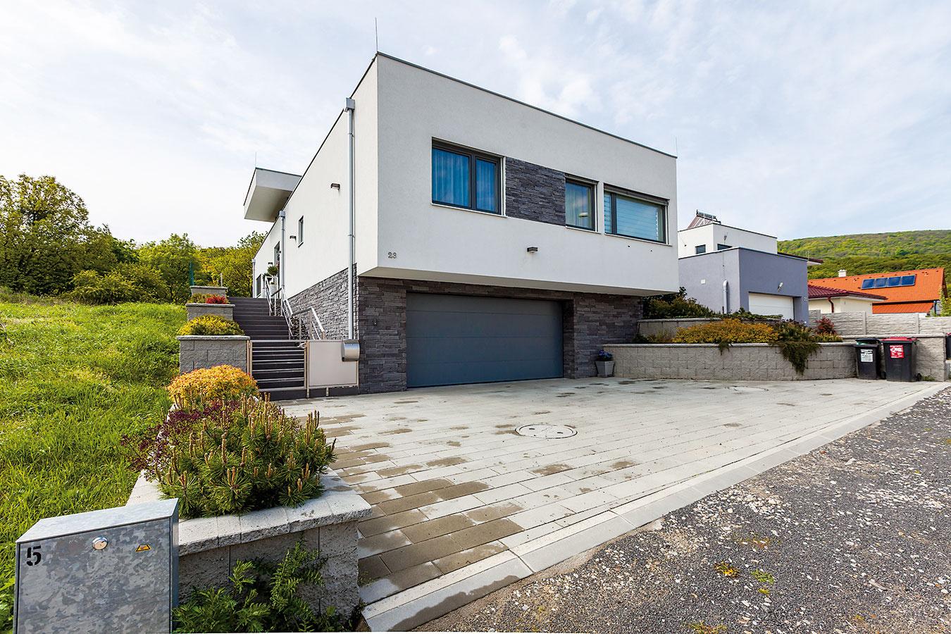 Nenápadnú bielu fasádu rodinného domu dekoruje sivý kamenný obklad.