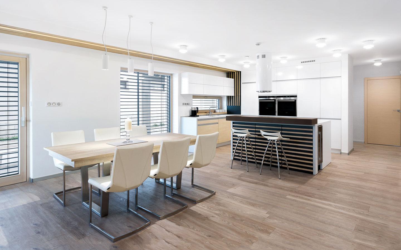 Drevené hranoly vblízkosti okien umne zakrývajú prieduchy núteného vetrania apôsobia aj mimoriadne dekoratívne. Systém prechádza celou dennou časťou – od kuchynskej linky ksedacej súprave ajeho súčasťou je aj LED osvetlenie.