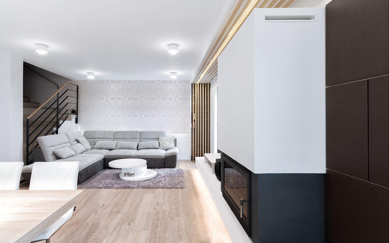Obývacia časť nie je zbytočne zaťažená nábytkom aprevládajú vnej odtiene sivej. Priestor zjemňuje vzorovaná tapeta anechýba zabudovaný kozub, ktorý spríjemňuje studené zimné dni.