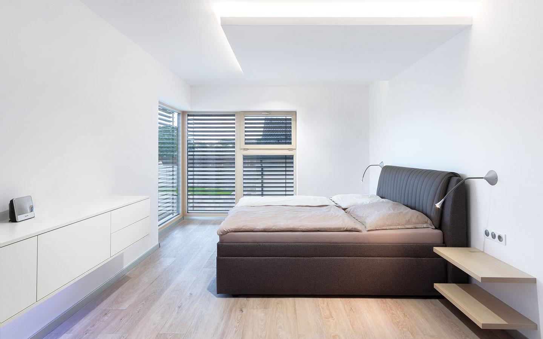 Čisto zariadenej rodičovskej spálni dominuje masívna čalúnená posteľ anechýba ani priestranný šatník. Cez rohové okno si môžu majitelia priamo zpostele vychutnávať výhľad do záhrady.