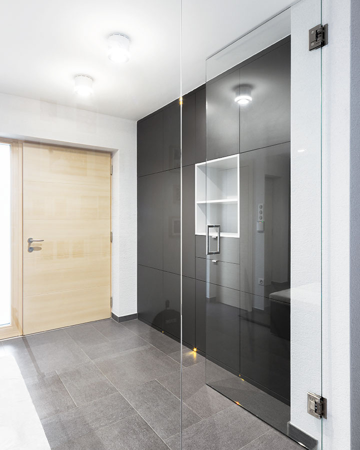 Po vstupe do domu privítajú hostí veľké zasklené dvere, ktoré podporujú pocit otvorenosti. Dajú sa otvárať vrozmedzí 180° aopticky presvetľujú aprepájajú vstup do domu spriestorom chodby.