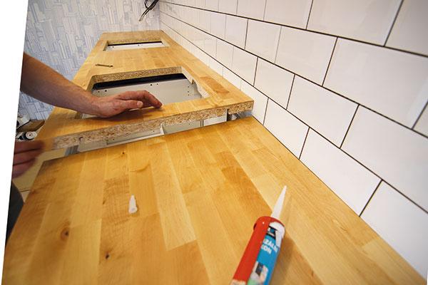 Kuchynská linka má 5 metrov a v tejto dĺžke sa pracovná doska nevyrába, preto ju bolo nutné zlepiť z dvoch kusov. Nezabudli ani na vytmelenie spoja medzi dvoma časťami dosky, aby sa doň nedostala voda.
