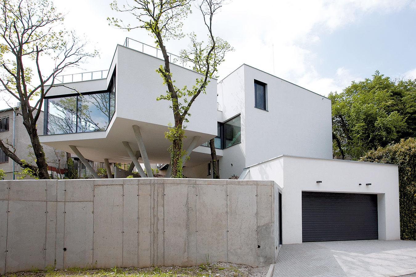 Zpohľadu ulice sa snaží dom nepútať pozornosť, čo sa mu vďaka neutrálnym materiálom aveľkému množstvu zelene aj podarilo.