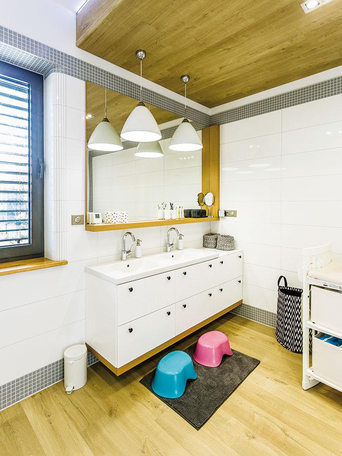 Dvojité umývadlo je pri zariaďovaní rodinnej kúpeľne praktickým riešením rannej špičky pri umývaní zubov. Znížený podhľad obložený drevom-, zhodným stým na podlahe celý priestor zjemnil.