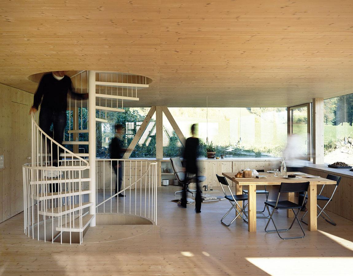 Moderné a zmysluplné. Celé prízemie tvorí jediný otvorený priestor, ktorý slúži ako obývačka, jedáleň, kuchyňa, herňa aj pracovňa. Zasklené plochy na všetkých štyroch stranách podporujú dojem vzdušnosti adrevo, ktoré architekt využil nielen na stenách, stropoch apodlahách domu, ale aj na výrobu vstavaného nábytku, zasa umocňuje dojem pokojnej jednoliatosti. Výhľad do okolia tak pôsobí ešte intenzívnejšie.