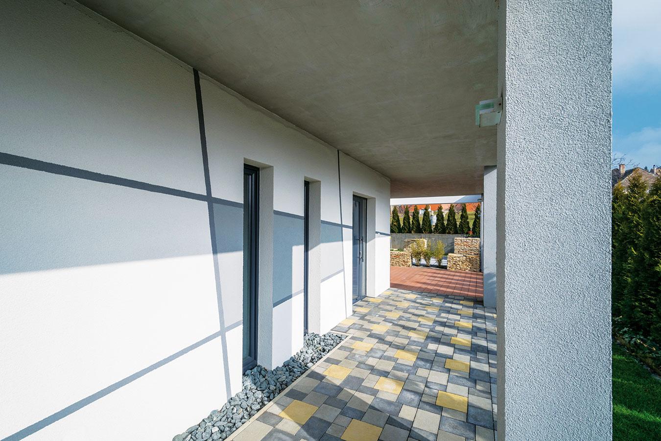 Decentná kombinácia sivej abielej kraľuje farebnému riešeniu fasády, dlažieb iďalších prvkov vexteriéri. Vmiestach, kde strecha presahuje ponad chodník popri dome aprekrýva terasu, je vstyku použitá výstuž sprerušeným tepelným mostom.