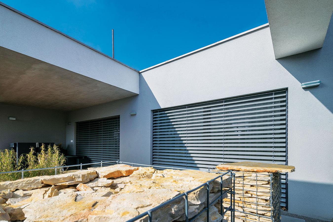 Štruktúra afarba gabiónov voplotení neveľkého pozemku príjemne dopĺňa minimalistickú fasádu moderného bungalovu.