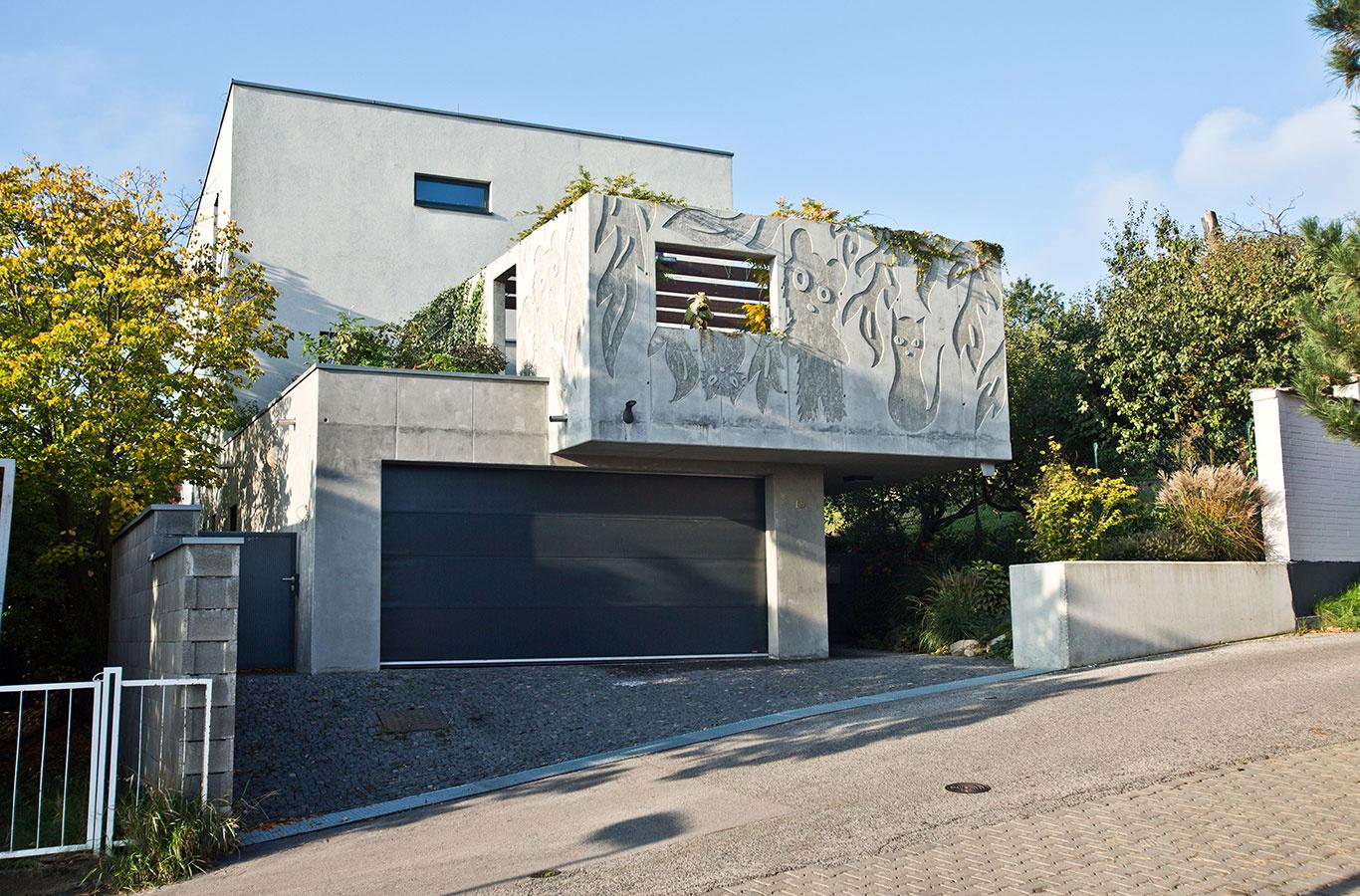 Trojpodlažný rodinný dom má od ulice odstup, aby nezatienil stavbu na susednom pozemku – vďaka tomu je pred garážou v úzkej ulici väčší manévrovací priestor. Z dôvodu preslnenia je pred domom len prízemná garáž, ktorá má na časti strechy bylinkovú strešnú záhradku.