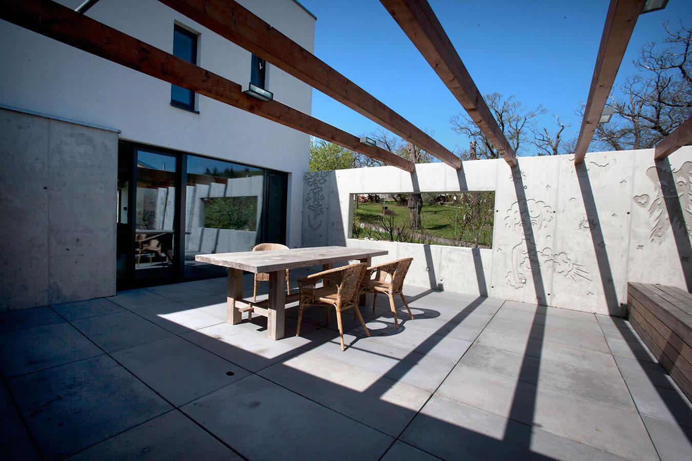 Severná terasa či skôr patio chránené stenami z grafického betónu poskytuje v lete príjemný tieň. Drevená konštrukcia nad terasou je naplánovaná ako opora pre vistériu, ktorá tu časom vytvorí ešte príjemnejšiu mikroklímu.