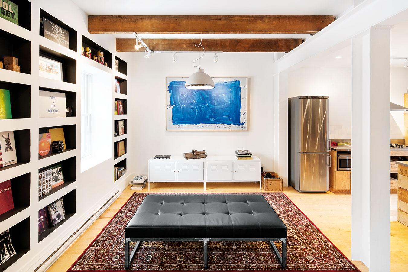 Obývačka netradične. Priestor obývačky vyriešili autori trochu neobvykle – namiesto klasickej pohovky zvolili univerzálne využiteľné jednoduché sedenie bez operadla, televíziu nahradil obraz supokojujúcou modrou farbou.