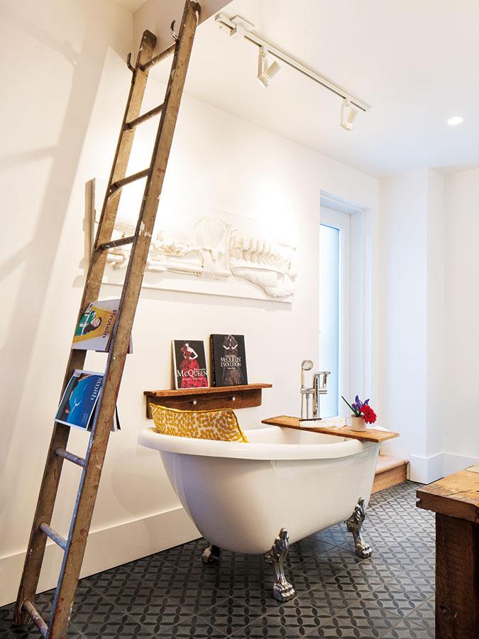 Pôvabná kúpeľňa chytí za srdce. Kombinácia rustikálnej dlažby, historizujúcej vane avešiaka zo starého dreveného rebríka priam vyžaruje domácku pohodu azvádza ponoriť sa do bublín spohárikom vína vjednej ruke aknihou vdruhej.