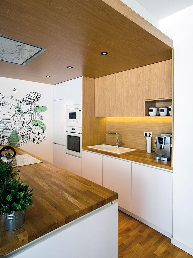 """Presunutím varnej zóny na kuchynský ostrov vznikla nevyhnutná pracovná plocha medzi drezom achladničkou, nutné však bolo vyriešiť odsávanie. """"Rozhodli sme sa vytvoriť drevený podhľad, ktorý na jednej strane vymedzuje kuchynskú časť asúčasne je doň zabudovaný stropný odsávač pár,"""" ozrejmuje architektka."""