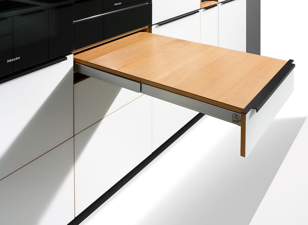 Zvonku nenápadná zásuvka ukrýva šikovnú výsuvnú pracovnú dosku. Oceníte ju napríklad v stiesnenejších bytoch s malou priamou kuchyňou, v ktorej je každý centimeter navyše naozaj žiaduci.