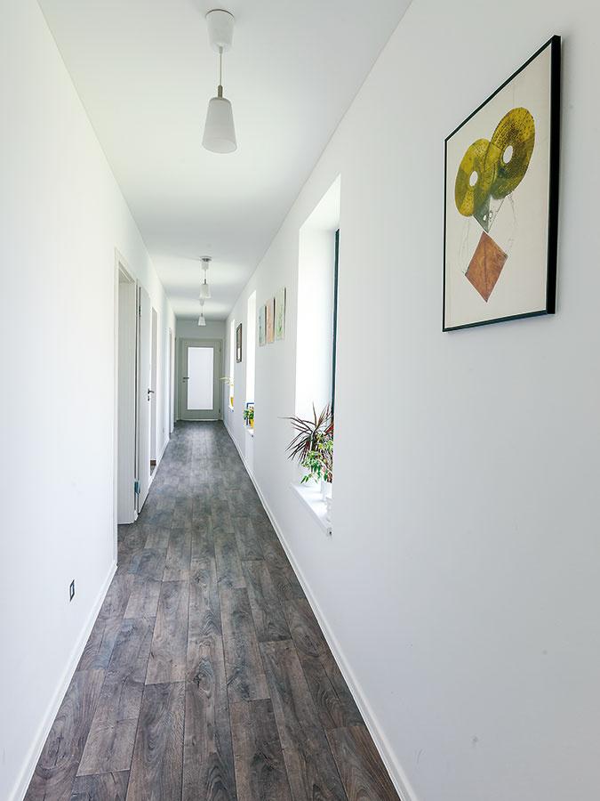 Cestou do obývačky treba prejsť chodbou pozdĺž celého domu, preto znej chcel architekt urobiť čo najpríťažlivejší vstupný priestor. Okná ju presvetlili aopticky skrátili, ich nízke široké parapety slúžia ako poličky alebo sa dajú využiť na sedenie, na stenách medzi oknami je miesto na fotografie aobrázky.