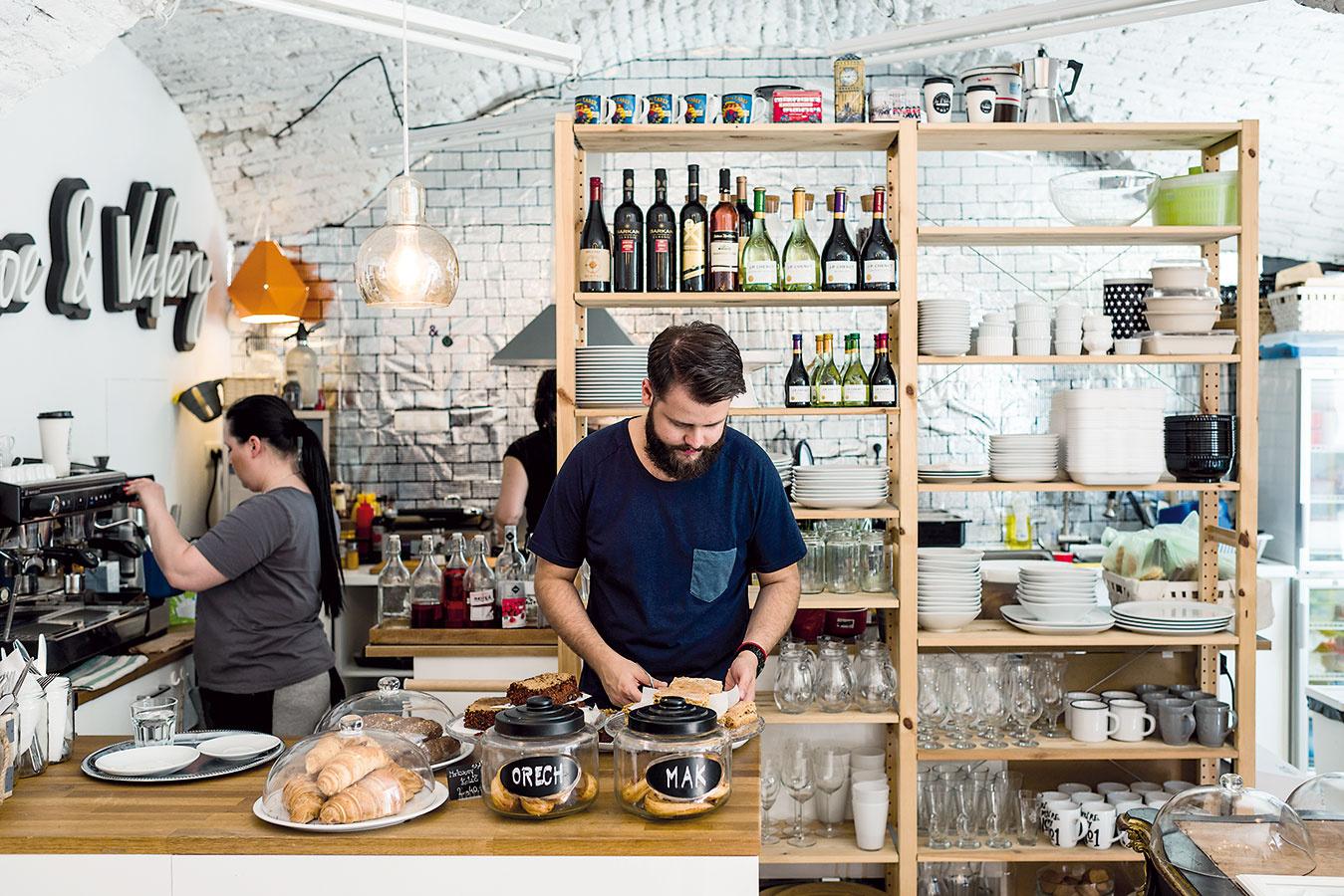 Kuchyňa je prepojená sbarom, ateda vsamom centre diania. Jednoduché drevené police tu poslúžia na uloženie pohárov, riadu aj ponúkaných nápojov azároveň kuchyňu čiastočne opticky oddelia od baru.