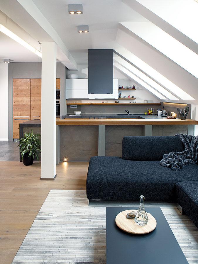 Umiernený interiér rozhodne nehýri farbami – ak nepoužila priamo sivú, volila dizajnérka takzvané odsýtené odtiene, teda také, ktoré obsahujú veľký podiel sivej. Vkontraste so sivou použila vobývačke teplú zlatistú farbu dubového dreva abielené dubové podlahy.