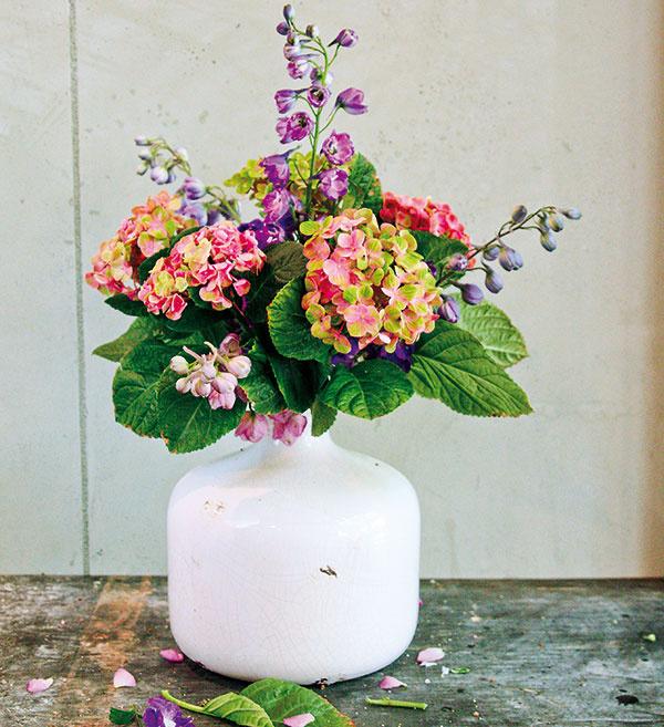 Elegantná keramická váza pôsobí aj napriek bielej farbe pomerne mohutne adominantne. Aby vnej aranžmán úplne nezanikol, uprednostnite pred subtílnymi lúčnymi kvietkami skôr mohutnejšie druhy svýraznými kvetmi, napríklad hortenziu (Hydrangea), ktorú môžete doplniť stračonôžkou (Delphinium).