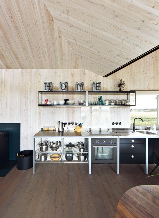 Industriál vs. príroda. Pretože vo vnútri už bolo dreva a jednoliatych plôch dosť, chcela architektka interiér odľahčiť a zvolila kuchynskú linku v antikorovom prevedení s otvorenými policami.