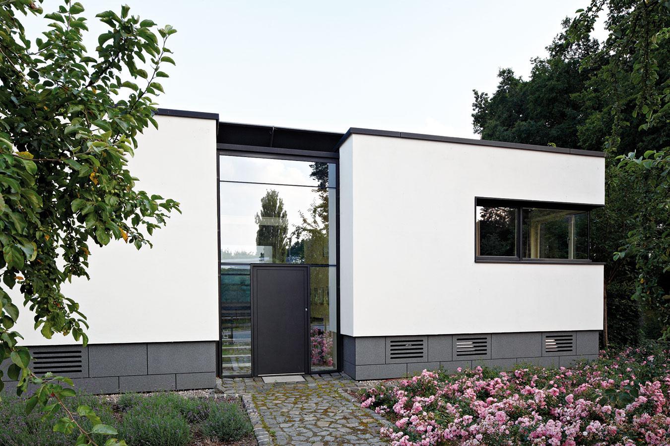 Smerom do ulice je objekt uzavretejší, čím zaisťuje želané súkromie. Oživením jednoduchej fasády je sklenený portál apásové okná selegantnými detailmi – sceloskleneným vyhotovením rohov asubtílnymi okennými profilmi (otváravé prvky majú pohľadovú šírku len 27 mm).