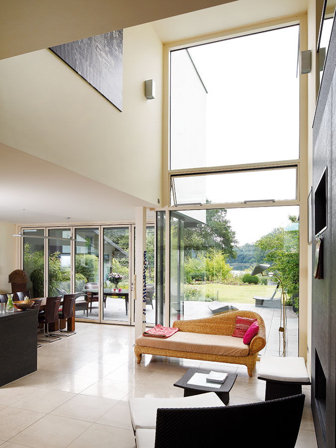 Nad obývačkou sa interiér otvára do výšky aprepája denný priestor na prízemí sposchodím. Impozantná sklenená fasáda tu poskytuje nerušený výhľad na jazero.