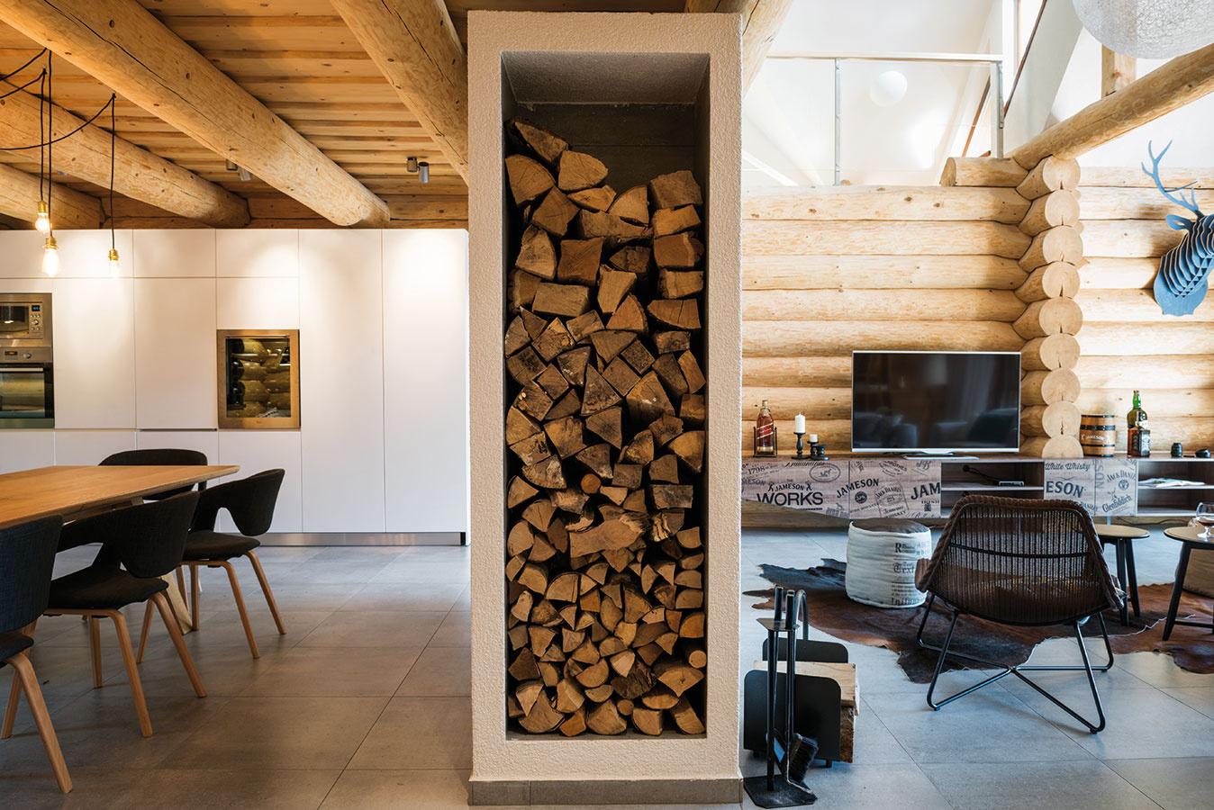Príjemná logika kozuba. Votvorenom spoločenskom priestore určuje kozub hranicu medzi obývačkou ajedálňou – vďaka obojstrannej vložke si možno voboch častiach užívať atmosféru ohňa. Bočná nika je praktickým miestom na uloženie dreva.