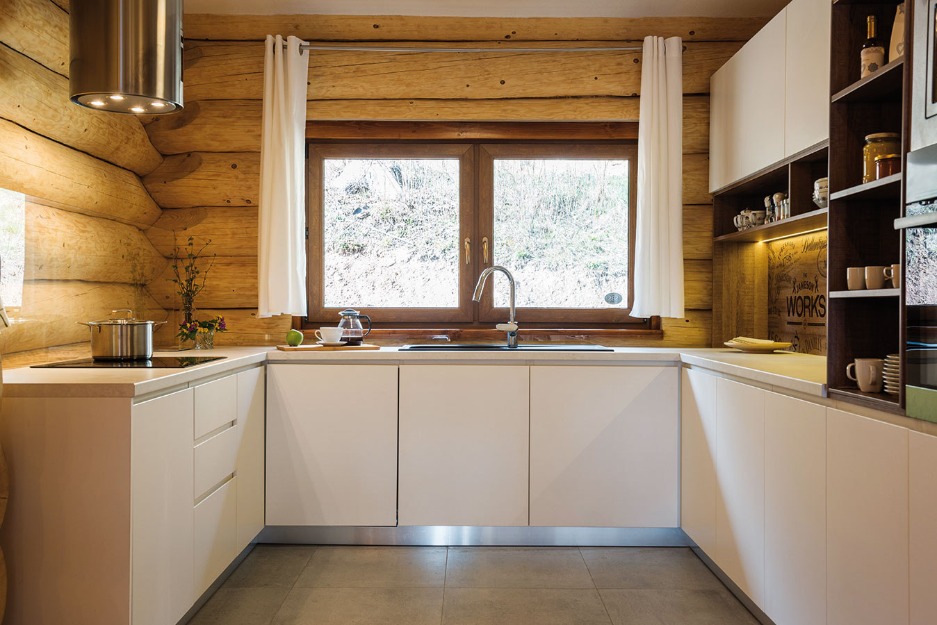 Sklenená zástena nenápadne chráni drevené trámy za linkou pred znečistením. Aj tento originálny prvok musel byť vyriešený ako konzola ukotvená klinke, tak, aby sklo nebolo zviazané so stenou.
