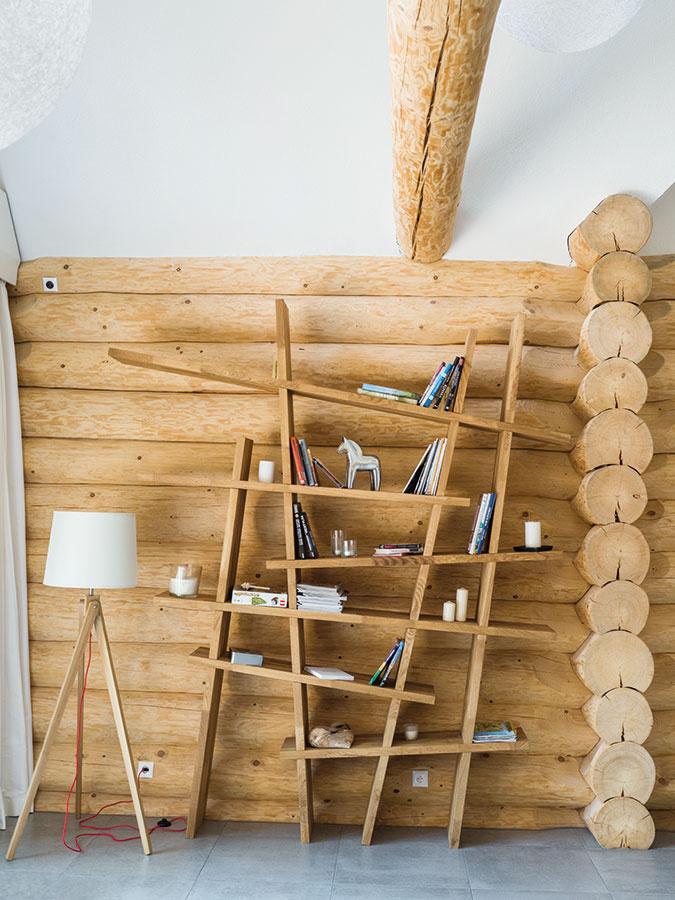 Atypická knižnica komunikuje vďaka materiálu sokolitými stenami, formou sa však vyčleňuje. Funguje ako skladačka uchytená na koľajničkách, ktoré umožňujú sadanie nosnej steny za ňou. Aby sa drevo nekrútilo, použili lepený dubový masív.