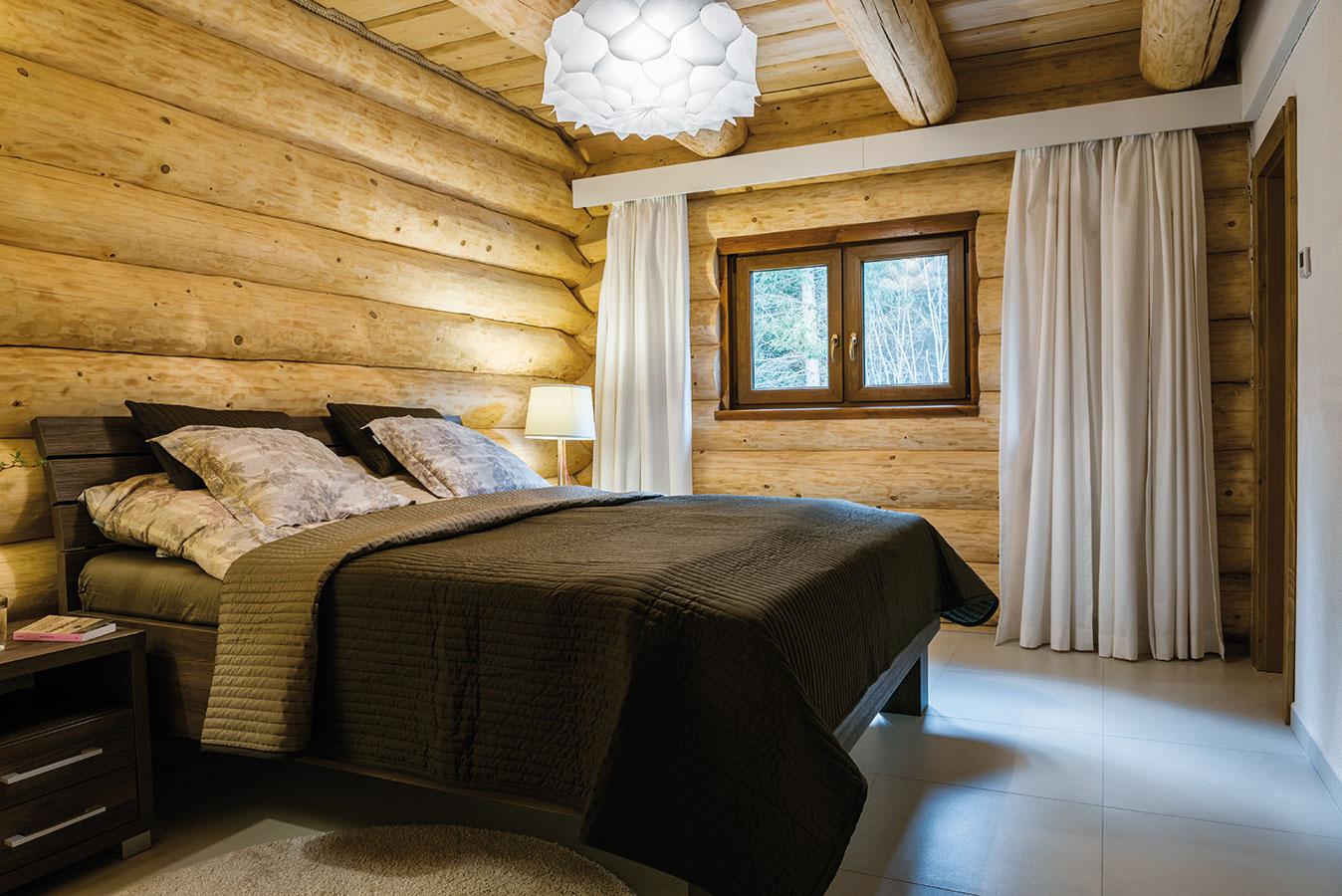 Hlavná spálňa je zariadená jednoducho aúčelne. Zariadenie, svietidlá atextílie vpokojných tónoch hnedej, sivej abéžovej navodzujú spolu sovšadeprítomným drevom pocit útulnosti.