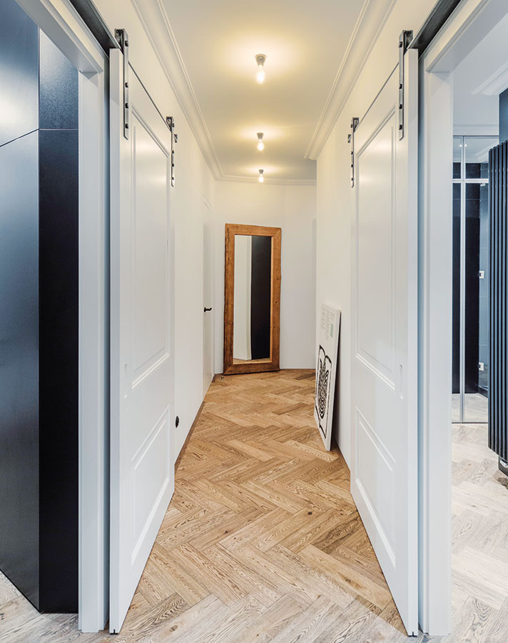 Posuvné dvere sdekoratívnymi kazetovými prvkami avýrazným kovaním, vďaka ktorým pôsobí chodba mimoriadne vzdušne, sa vyrábali na mieru. Vrovnakom duchu sa nesie aj obloženie stien, ktoré bolo vminulosti jedným zcharakteristických znakov starých meštianskych domov.
