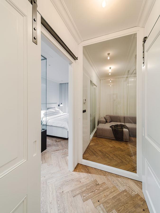 Posuvné dvere so sklenenou vitrážou sú ukryté vnike. Ak chce majiteľ priestor obývacej časti achodby oddeliť, postačí ich jednoducho vysunúť.