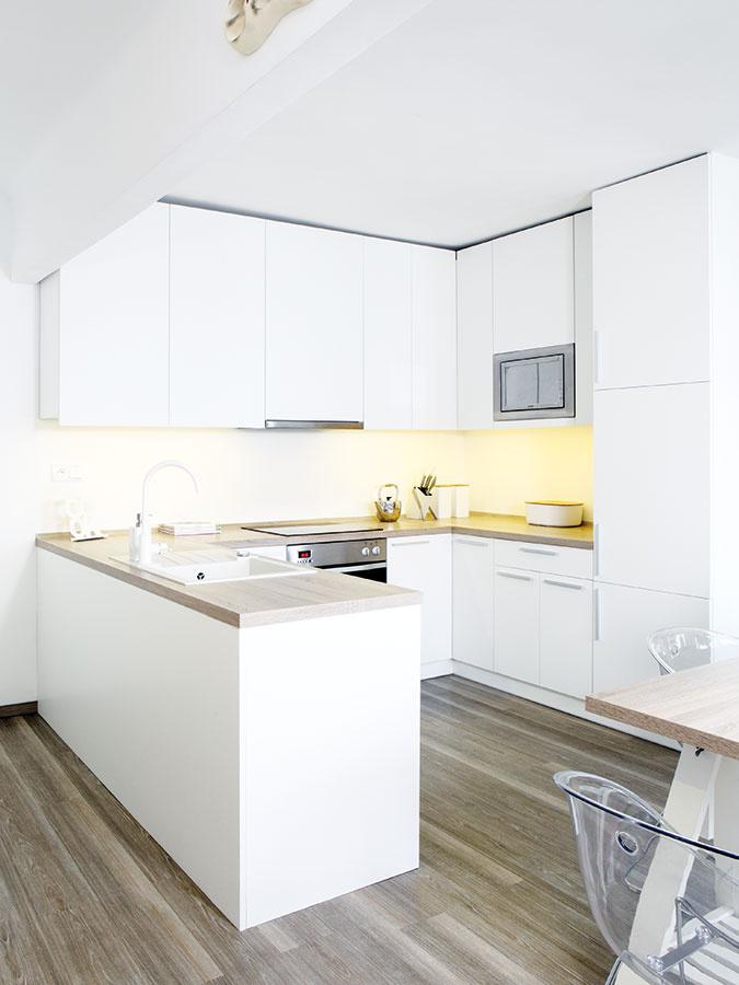 """Kuchyňa  vo väčšom """"zálive"""" pri vstupnej chodbe poskytuje dostatok miesta na prácu aj na odkladanie. Prakticky na ňu nadväzuje jedálenský stôl."""