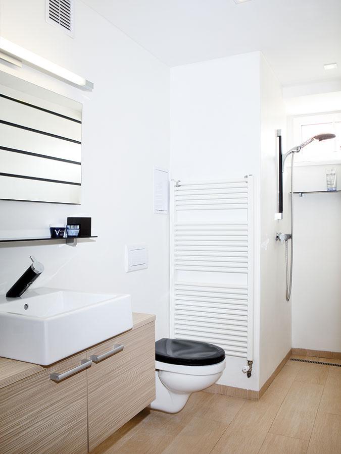Aj dispozícia kúpeľne sa celkom zmenila. Výklenok, kde bolo predtým umiestnené WC, dnes slúži ako sprcha, ktorá voľne nadväzuje na priestor kúpeľne.