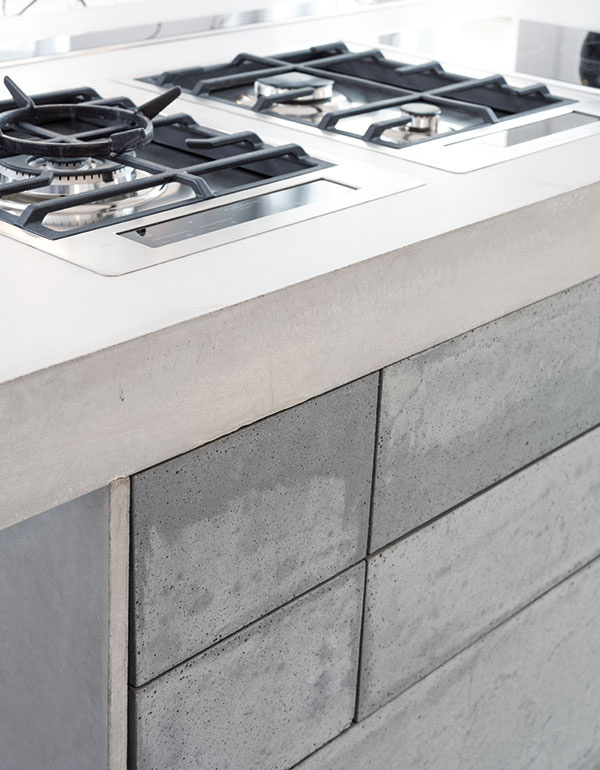 Technológia FixCrete® od štúdia Gravelli zabezpečuje vysokú pevnosť betónu, vďaka ktorej možno vytvárať prvky od hrúbky steny 15 mm. Takto upravený betón je až osemkrát ľahší ako ten klasický a možno ho rozmanito tvarovať, čo v prípade pracovnej dosky umožňuje vsadenie napríklad varnej dosky, drezu či vínotéky.  (foto: Martin Zeman, návrh interiéru OOOOX)