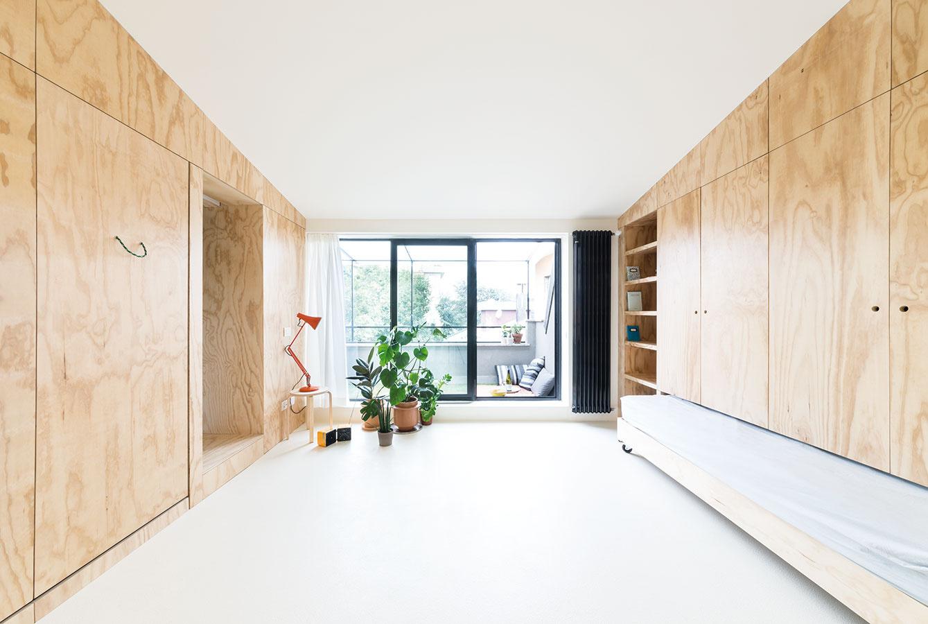 """Dva """"aktívne"""" preglejkové panely na stenách ukrývajú dvojlôžko, posuvné dvere vedúce do kuchyne akúpeľne, šatník aj klimatizačnú jednotku."""