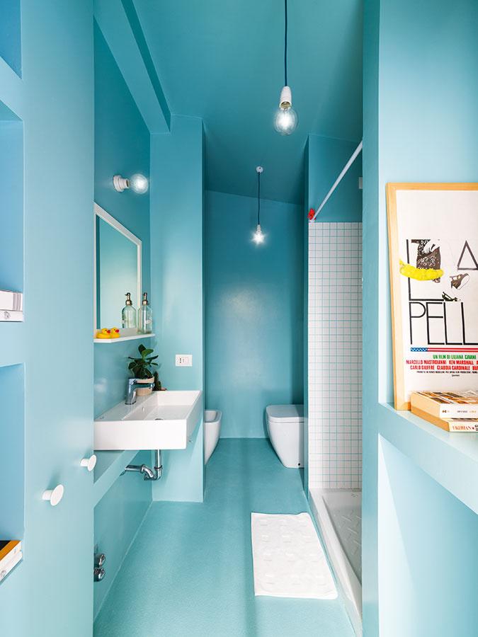 Kúpeľni dominuje rovnako ako kuchyni modrá farba doplnená bielou. Sympatickým detailom sú škáry vsprchovom kúte,  pri ktorých architekti zvolili rovnaký odtieň modrej ako na steny apodlahu.