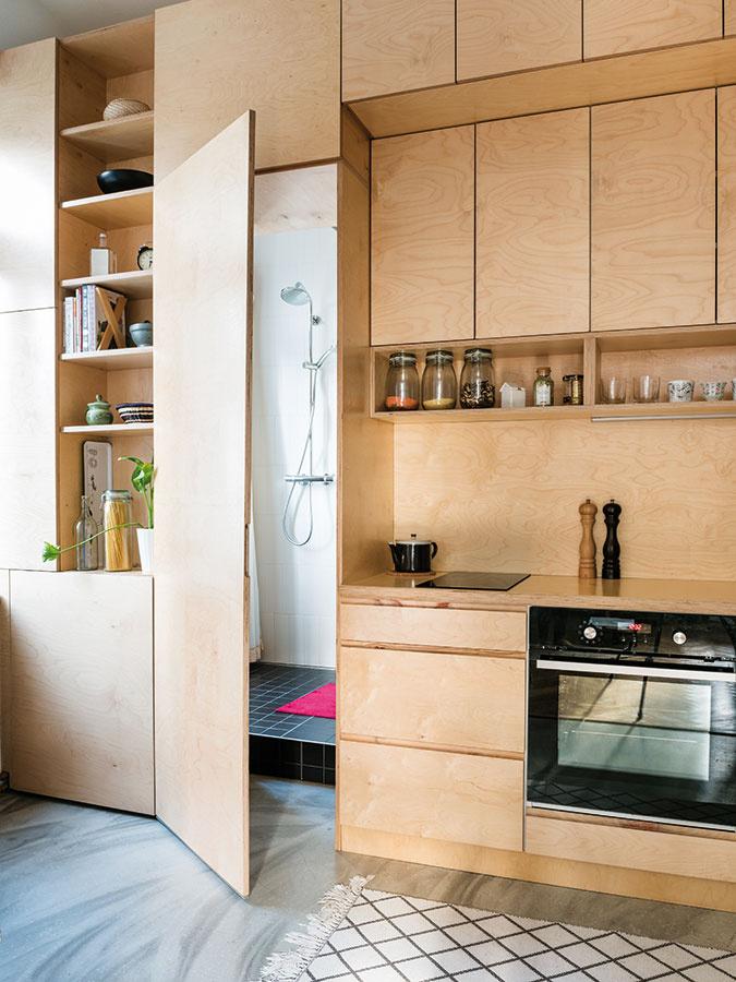 Skriňa alebo dvere? Kuchynská linka v byte, ktorý navrhli architekti z ateliéru NOØ, je celá z preglejky. Použili ju na pracovnú dosku aj kuchynskú zástenu, nevyhnutná ale bola vhodná povrchová úprava. Za dverami, ktoré na prvý pohľad pripomínajú potravinovú skriňu, sa ukrýva kúpeľňa.