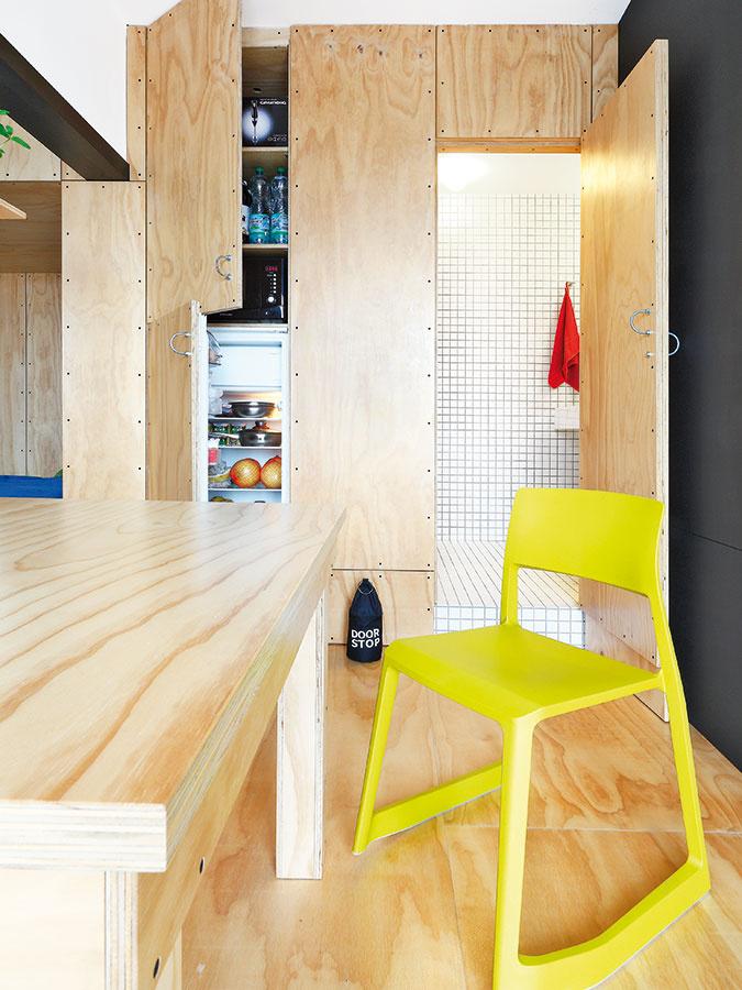 Materiálová jednota. Potravinové skrine v kuchyni, stôl aj podlaha. Preglejka nenudí ani v prípade, že sa v priestore zopakuje na viacerých prvkoch tak ako v kuchyni, za ktorou stoja toito architekti. Dávku dynamiky môžete do priestoru dodať napríklad farebnejšími kusmi nábytku a doplnkami.