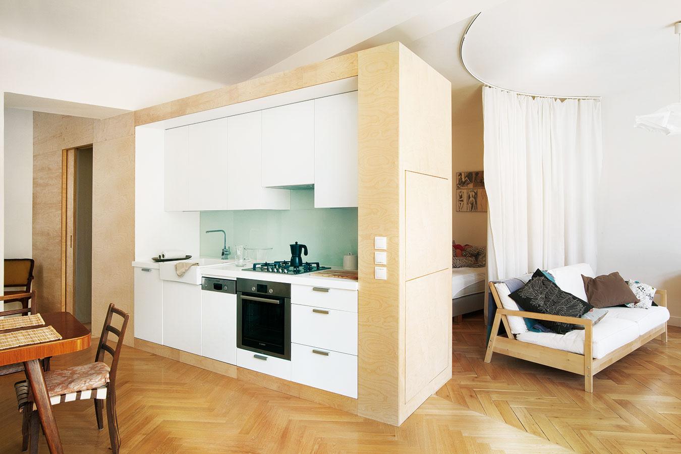 Viac ako len kuchyňa. Olejovaná brezová preglejka sa stala hlavným spojivom aj v byte z dielne pražských architektov edit!. Najvýraznejší prvok je kubus, ktorý z jednej strany obopína kuchynskú linku, z druhej vytvára knižnicu a na čelnej strane ukrýva aj nenápadný bar s výklopným pultíkom.
