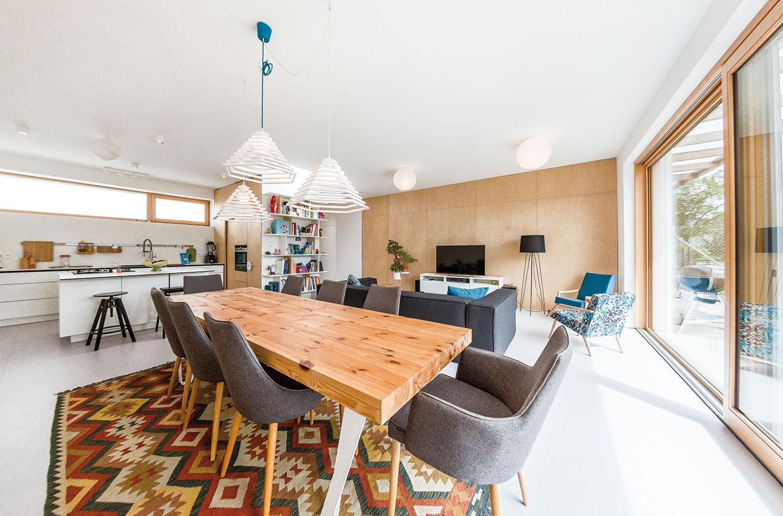 Priestor pre spoločnosť. Obývačka spojená sjedálňou, kuchyňou aj so záhradou – dôležitou požiadavkou majiteľov bol otvorený denný priestor, kde by sa mohli stretávať spočetnou rodinou apriateľmi. Vnovom dome sa im ju podarilo perfektne naplniť.