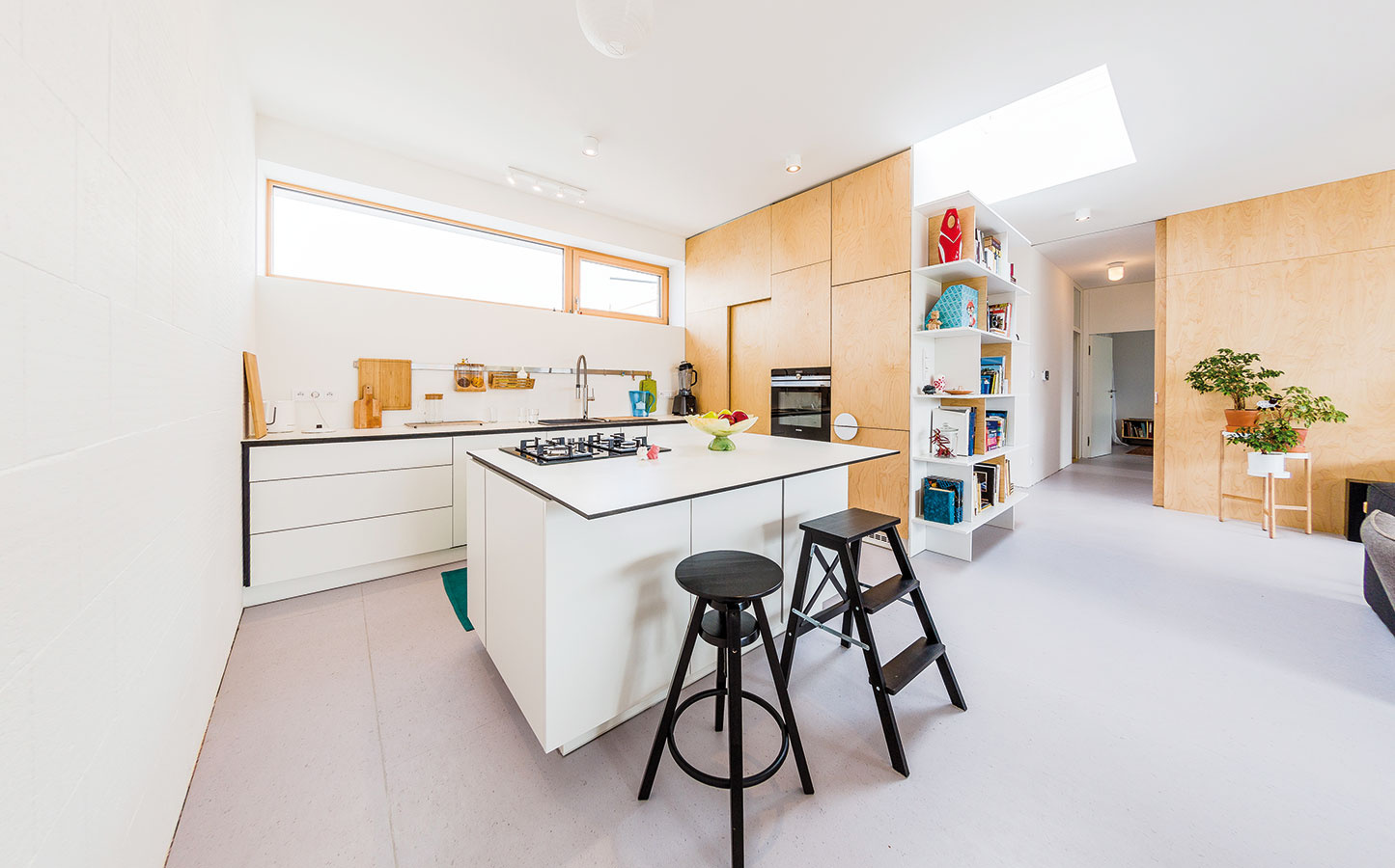 Charakteristickým prvkom dennej zóny je preglejkový obklad – ozvláštňuje interiér azároveň vytvára prepojenie medzi časťami sodlišnou funkciou. Svetlé drevo príjemne doplnilo biele steny apodlahy zprírodných materiálov (linoleum akaučuk) apreteplilo moderný priestor.